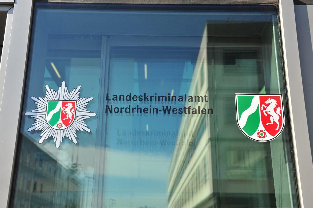 Glastür mit Aufdruck Landeskriminalamt NRW. Es spiegelt sich das Gebäude im Glas.