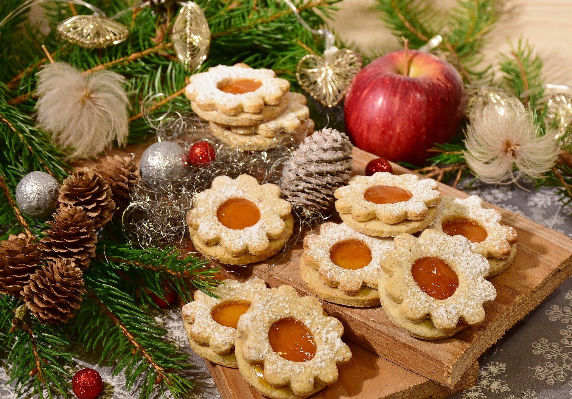 Weihnachtsplätzchen nett dekoriert auf einem Brett zwischen Tannenzweigen, tannenzapfen und einem Apfel